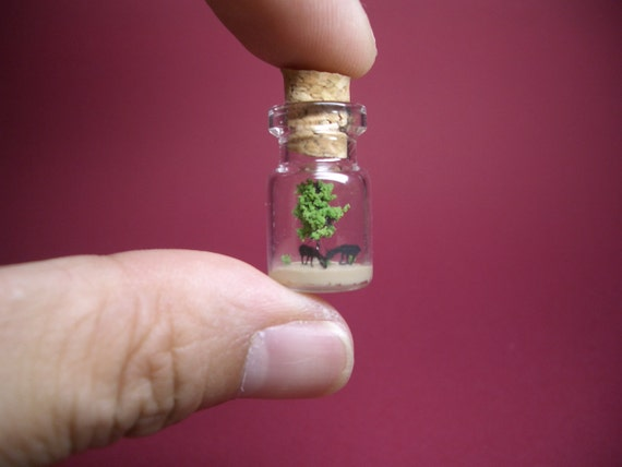 Horse are in front of the tree in a tiny bottle