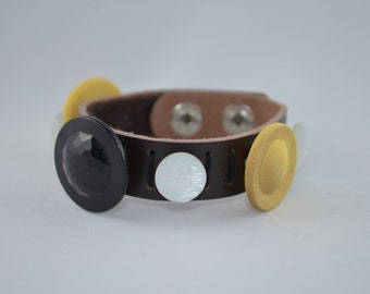 Brown leather bracelet with black, gold, & white vintage buttons