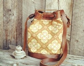 Leather and Canvas Round Bucket Messenger Bag With Bohemian Print In Brown, Gold and Orange Tones