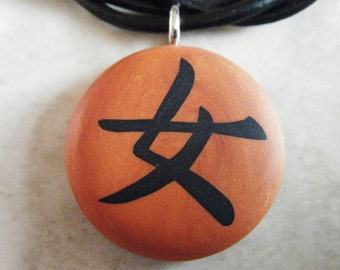 "Japanese kanji symbol for ""WOMAN"" hand carved on a polymer clay burnt orange color background. Pendant comes with a FREE necklace"