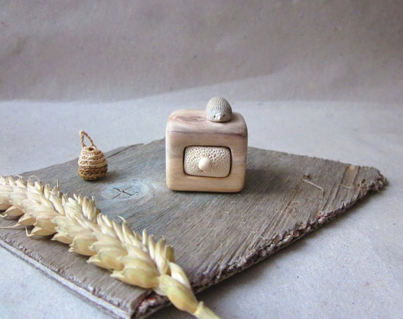 Miniature cabinet with a cute little hedgehog , wood carving