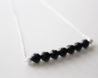 Penumbral Necklace --- seven sparkling faceted onyx rounds