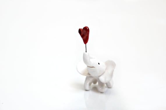Miniature elephant holding red heart
