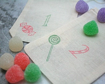Whimsical advent calendar set.  Set of 24 hand stamped muslin favor bags.  Playful numbers and candy, red and green.