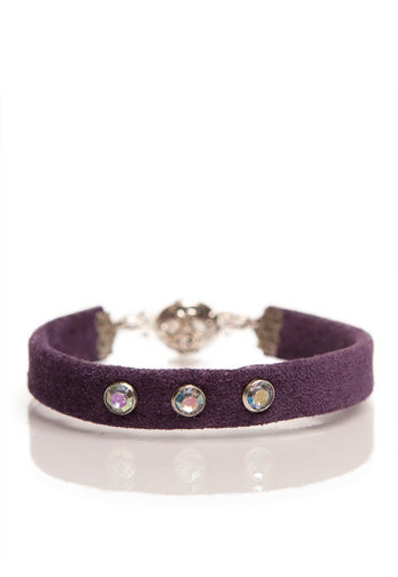 Suede bracelet adorned with riveted pearls.
