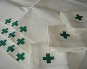 3 placemats and 3 cloth napkins featuring green embroidered cross