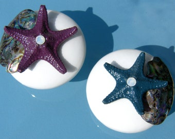 White Cabinet Knobs with Abalone shell pieces and knobby starfish in peacock blues and purples with opalescent accent.