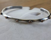 Single thin sterling cuff bracelet with hammered bronze studs