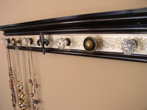jewelry/necklace  organizer with 7 decorative cabinet knobs on black with champagne embossed background 20  inches long