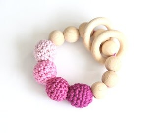Shades of pink. Pale pink, bright pink, berry teething ring toy with crochet wooden beads. Rattle for baby.