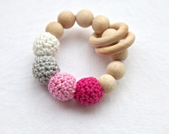 Pink, bright pink, grey and white ring toy with crochet wooden beads. Rattle for baby.