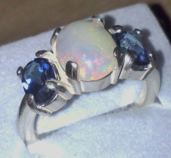 price lowered Ethiopian Opal Ring Light and Firey with two Sapphire Blue Topaz Gemstones in Sterling Silver