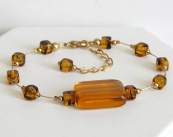 Gold nylon-coated stainless steel wire bracelet with amber glass beads and gold-plated round beads
