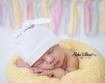 White newborn hat. Knot top style.  Adjustable. Size: Newborn/XS       (Made by lippy brand)