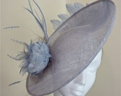 Pale grey/ blue sinamay saucer with pale blue feather flower, and a sweep of matching swan feathers on the underside