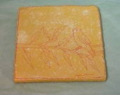 Yellow and red tumbled marble trivet with bird and tree branch