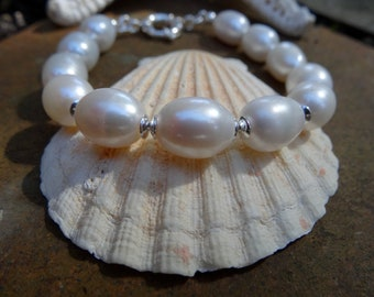 Smooth and shiny 12mm oval shape water pearls bracelet. Sterling silver 14 mm mariner clasp.