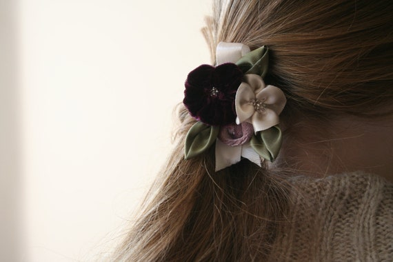 Flower hair clip. Fall preview. Purple velvet and cream satin beaded flowers with green silk leaves on a metal clip.