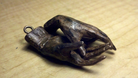 "Bronze sculpture 2"" long small bronze hands with bronze screw eyes,"