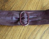 Vintage Omega burgundy colored wide leather belt with a coordinating metal buckle
