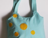 Turquoise Shoulder bag with yellow circlet.