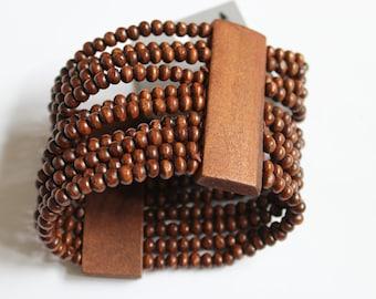 Handmade dark wooden cuff bracelet with small beads.