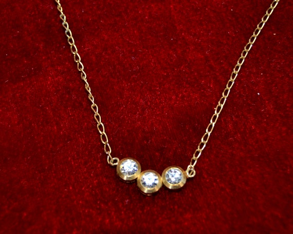 old gold necklace with three white stones placed together jewelryhad
