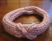 Pink knit headband embroidered with one flower.