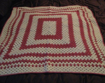 Bright pink and white granny square baby afghan