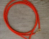 red wrap bracelet with gold charm