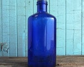 Blue antique bottle with cork candle