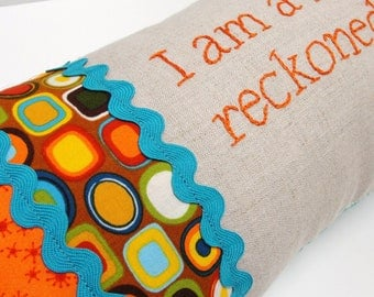 "Hand-embroidered pillow  ""I am a force to be reckoned with."" in orange, turquoise, brown"