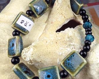 Stretchy bracelet with Blue/Green ceramic tiles, blue crystals, black beads, ocean colored bracelet