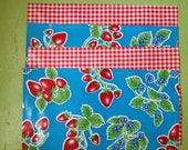 Reversible oilcloth placemats in a retro strawberries on vivid sky blue and red gingham