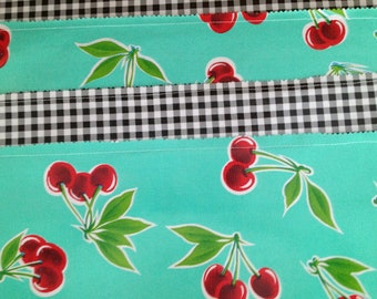 Reversible oilcloth placemats in a retro cherries on seafoam green