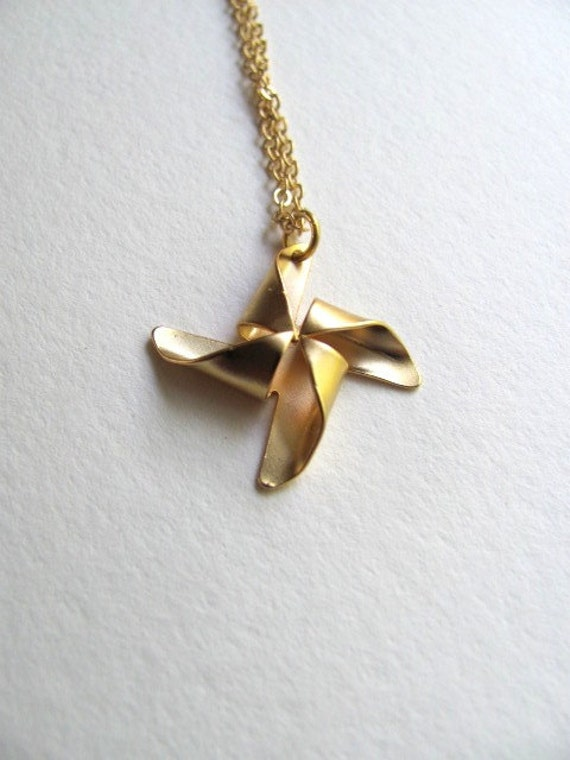 Petite gold pinwheel charm necklace on delicate 14k gold plate chain, satin matte finish