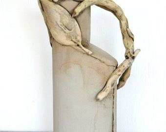 Sculptural earthenware pitcher with leaves and twigs