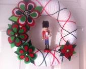 Handmade Holiday Yarn Wreath with a nutcracker -12 in wreath