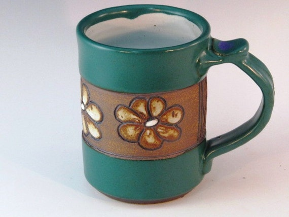 Green mug with flowers carved around center of pot.