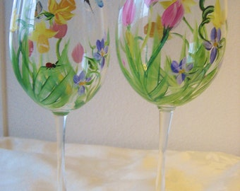 Set of two , handpainted wineglasses with Spring wildflowers, daffodils, tulips and violets.