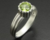 Modern design sterling silver ring with a round green peridot