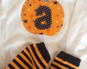 halloween pumpkin initial one piece and hand dyed striped baby leg warmers