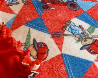 Fleece blanket,international little boy and tractor,other side is all red.. Will fit a gueen size bed..