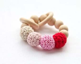 Pink, red, natural beige ring toy with crochet wooden beads. Rattle for baby.