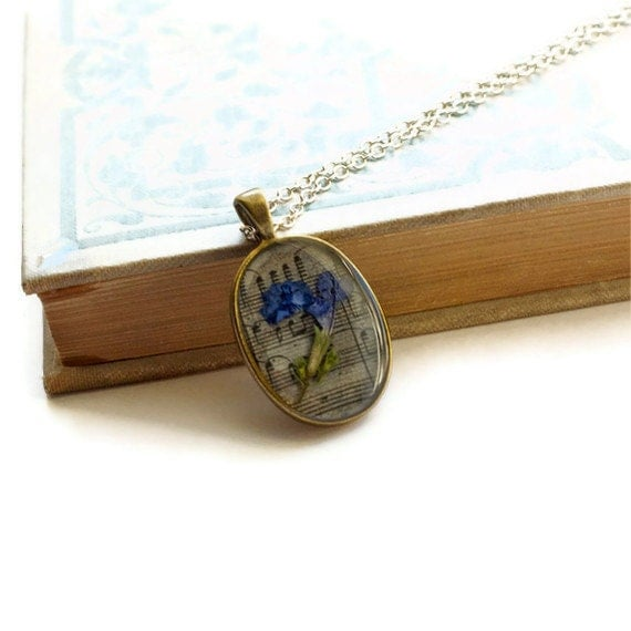 pressed flower necklace real resin blue wildflower botanical pendent. set onto music note paper.
