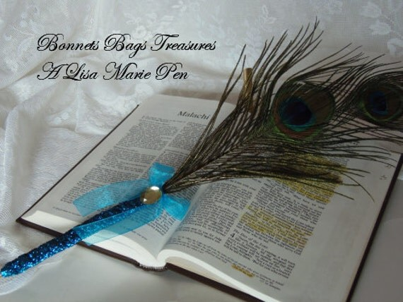 Peacock Feather Pen wrapped with greenish blue metallic ribbon accent yellow jewel and bow Black Ink writes smoothly on paper with no drag