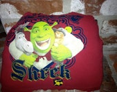 """Upcycled  """"Shrek"""" tshirt pillow in red featuring Shrek hugging Donkey and Puss in Boots with yellow trim on the bottom"""