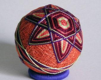 burgundy 6 point star on orange temari ball