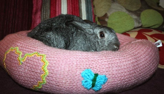 Ugli Donut bunny rabbit bed for a medium to large sized bunny pink hand knit with butterfly and strawberry appliques
