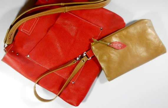 Leather shoulder bag in orange and gold with included wristlet clutch.